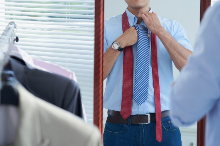 Cropped image of man adjusting tie before date