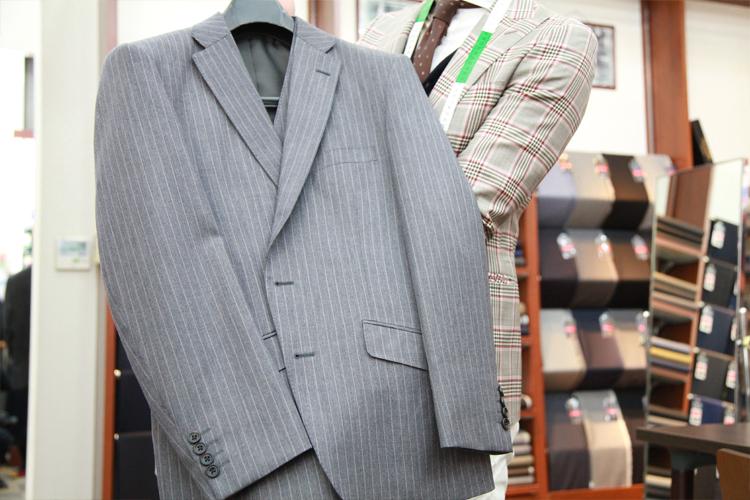 グレーにストライプ、スタンダードなデザインのスリーピースのスーツ