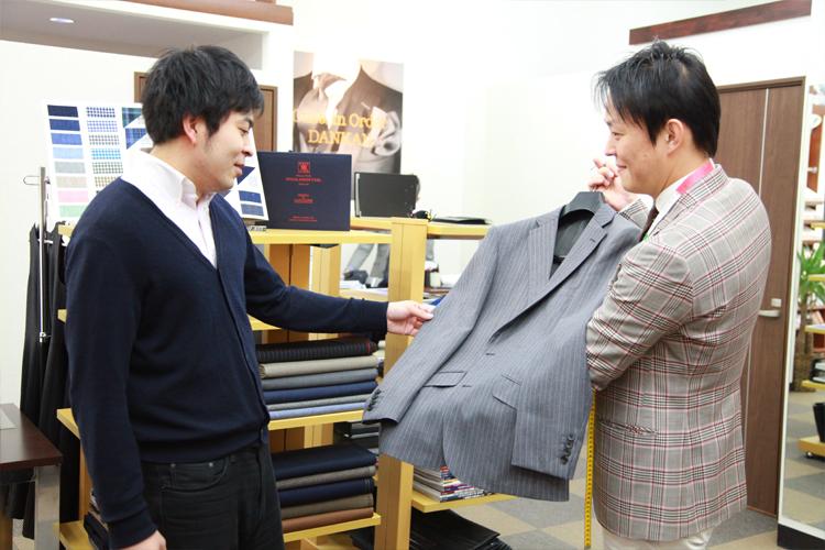 仕上がったスーツを手にした榮岩さんと植田